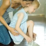 Mother watching daughter ties shoe laces